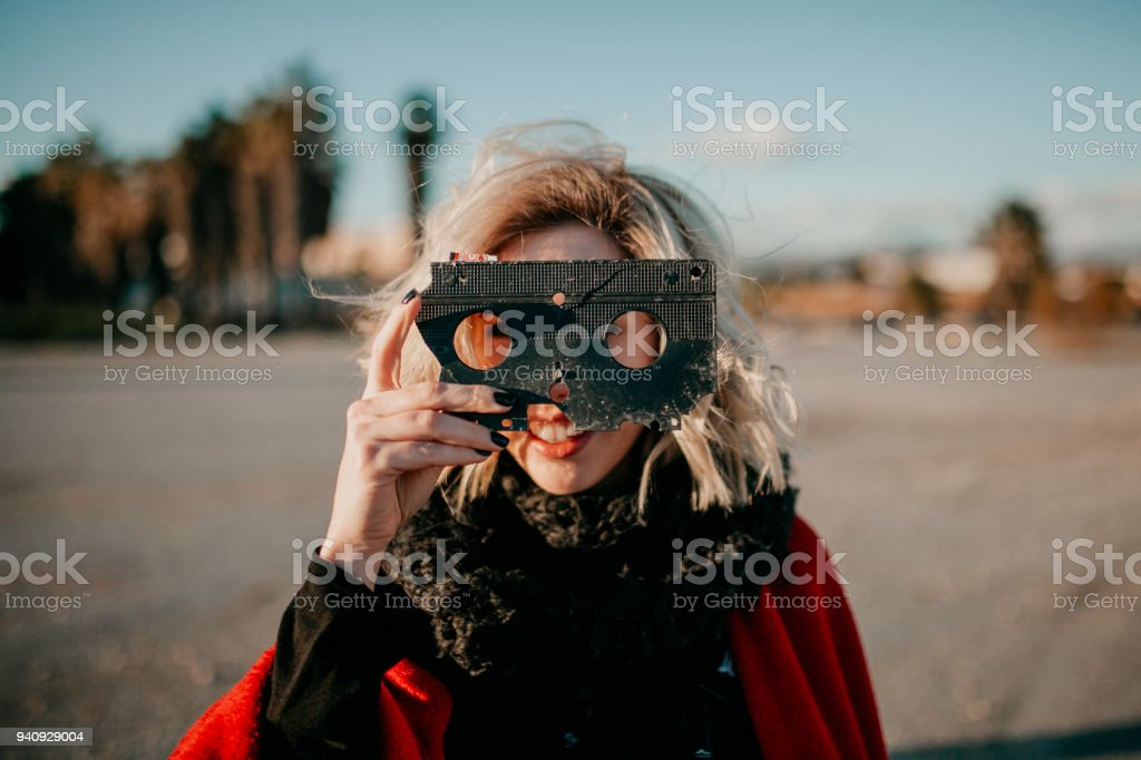 Blonde alternative woman playing with a VHS tape outdoors at sunset. Creative filmmaker concept. stock photo