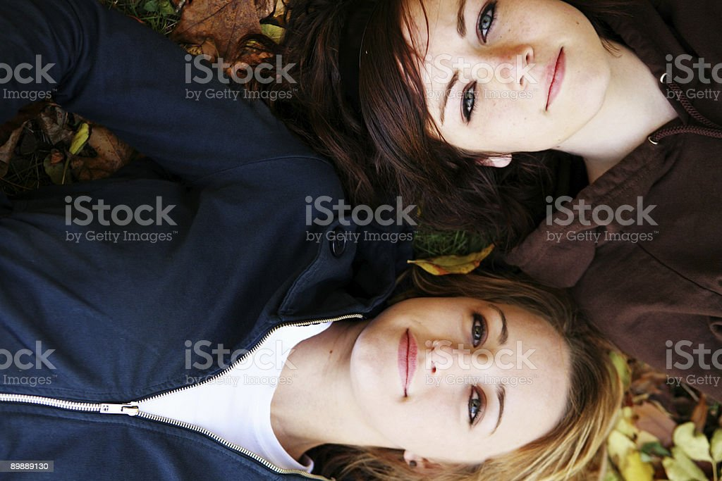 Blonde and Brunette Girls Lying in Autumn Leaves royalty-free stock photo