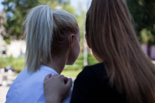 Blonde and brunette wearing ponytails stock photo