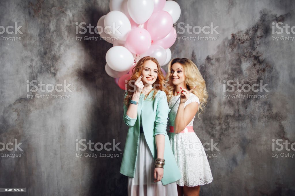 Blonde and redhead. Two young charming girlfriends at the party. Happy and cheerful girl with balloons. stock photo