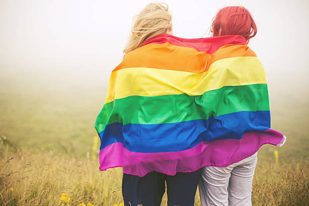blonde and redhead woman wrapped in rainbow flag - transsexual stock photos and pictures
