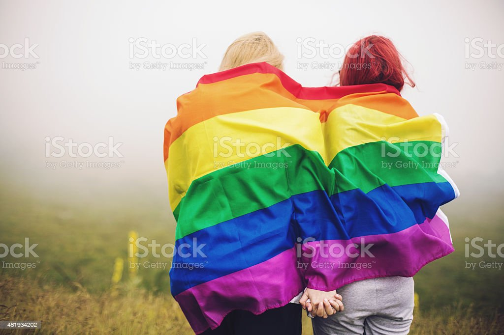 Blonde and redhead woman wrapped in rainbow flag stock photo
