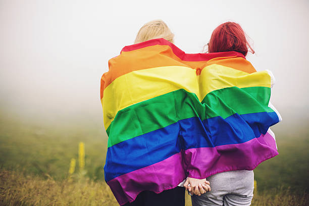 Blonde and redhead woman wrapped in rainbow flag Blonde and redhead woman wrapped in rainbow flag lgbtqi rights stock pictures, royalty-free photos & images