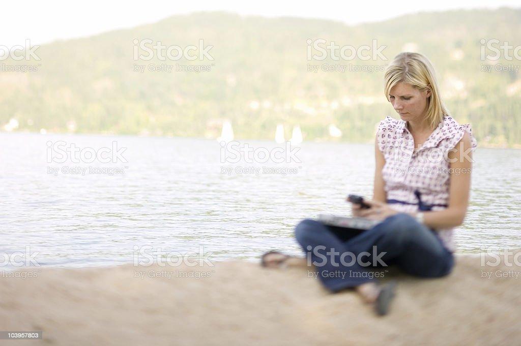 Blonde at lake using blackberry royalty-free stock photo
