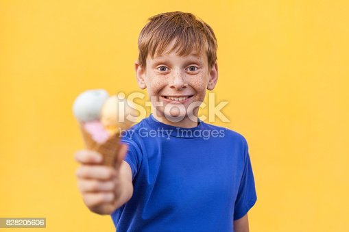 istock Blonde beautiful boy with freckles and blue T-shirt showing  ice cream  and looking at camera with big eyes and toothy smile. Studio shot, isolated on a yellow background. 828205606