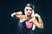 Portrait of young blonde woman in hip hop clothes, striking a muscle rebel pose, expressing vitality, courange and determination.