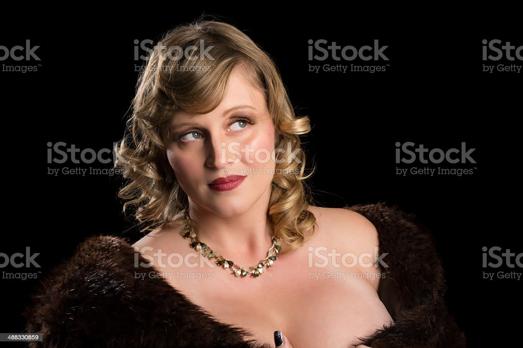 Blonde beauty in fur coat smiling, looking away. royalty-free stock photo