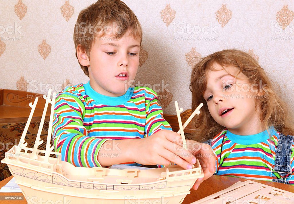 Blonde boy and girl make homemade wooden boat royalty-free stock photo