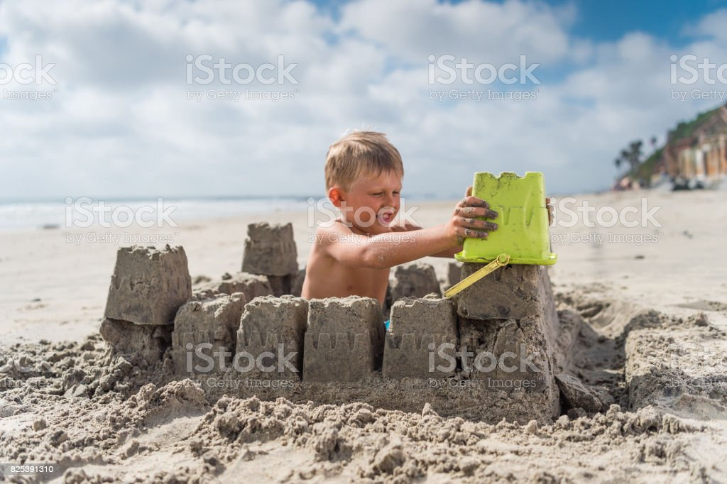Blonde Boy At The Beach Building A Sand Castle stock photo