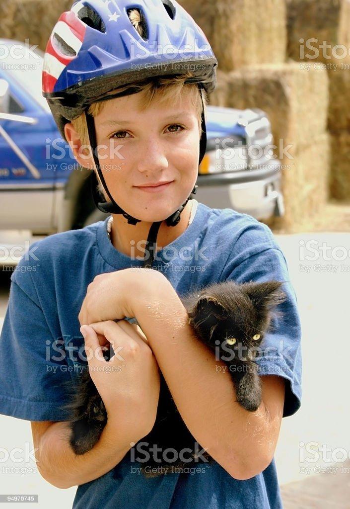 Blonde Boy Holding Black Kitten royalty-free stock photo