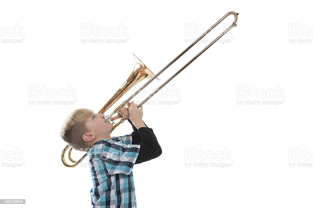Blonde boy playing the trombone. stock photo