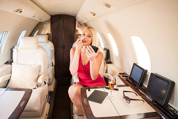 Blonde businesswoman applying makeup in private jet airplane stock photo
