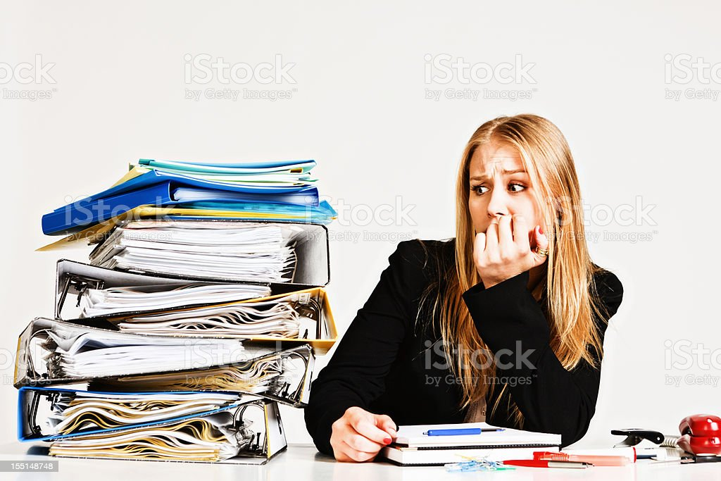 Blonde businesswoman bites nails worrying about work overload royalty-free stock photo