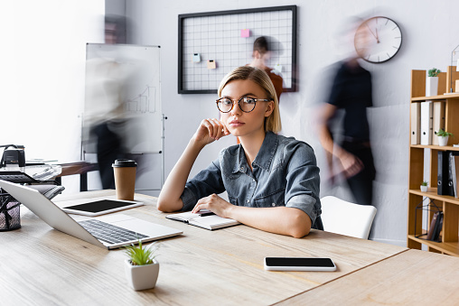 blonde businesswoman in eyeglasses sitting at workplace with gadgets in open space office, motion blur