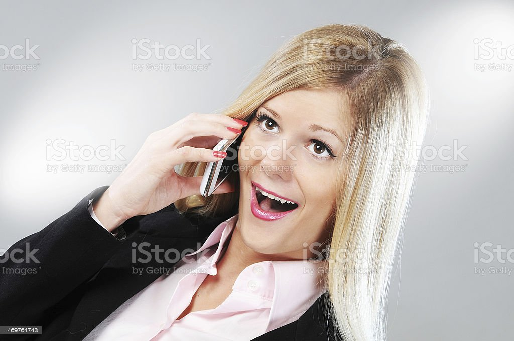 Blonde businesswoman in formal outfit using smart phone and smiling stock photo