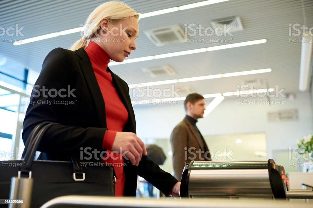 Blonde Businesswoman Passing Turnstile stock photo