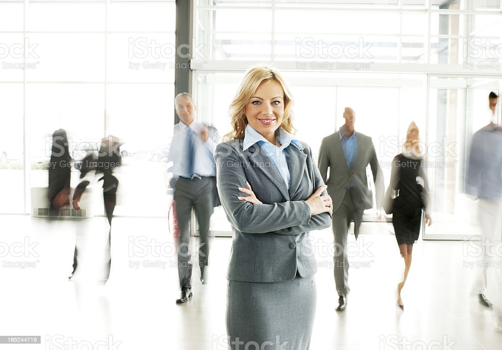 Blonde businesswoman  standing in the lobby with arms crossed. royalty-free stock photo
