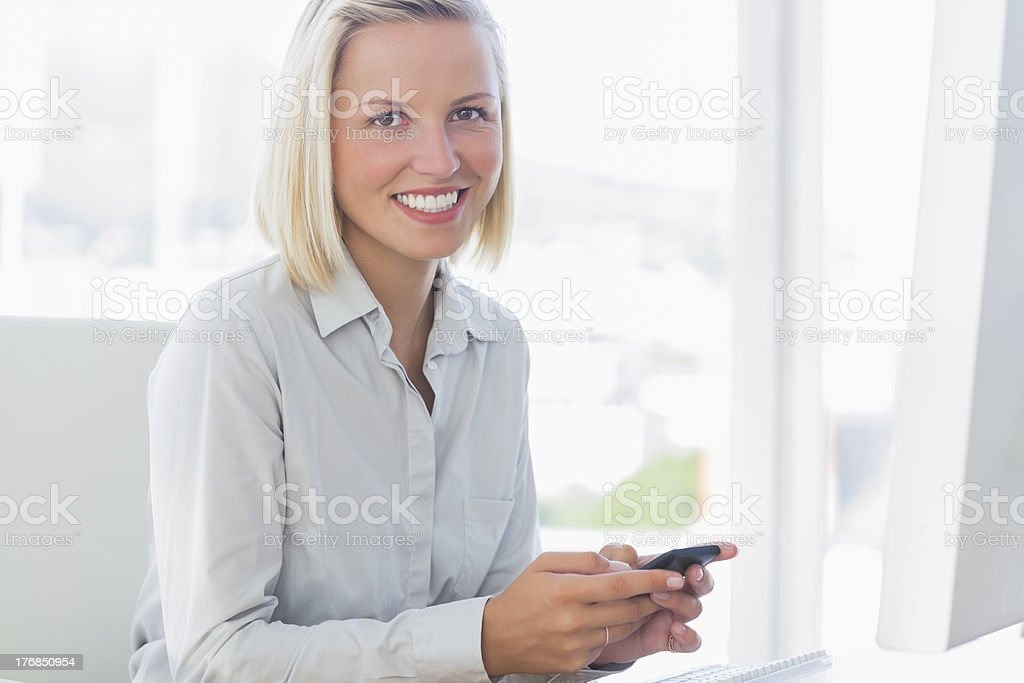 Blonde businesswoman texting and smiling at camera royalty-free stock photo