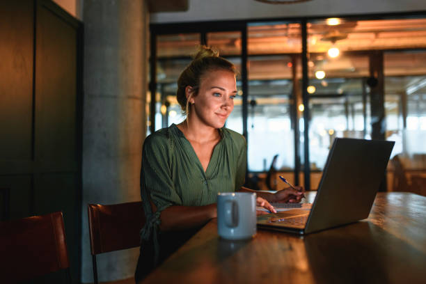 blonde businesswoman using laptop in dimly lit board room - dimly stock pictures, royalty-free photos & images