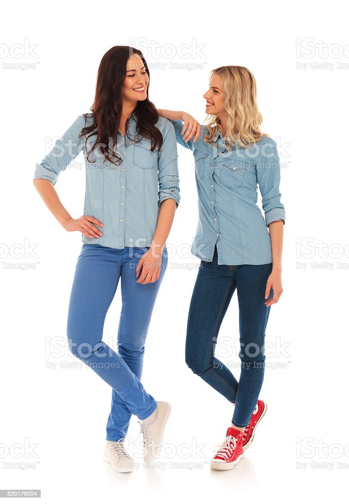 blonde casual woman leaning on her friend stock photo