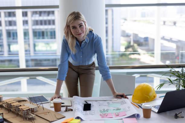 blonde kaukasische architektin schaut kamera am schreibtisch im büro an - architekturberuf stock-fotos und bilder