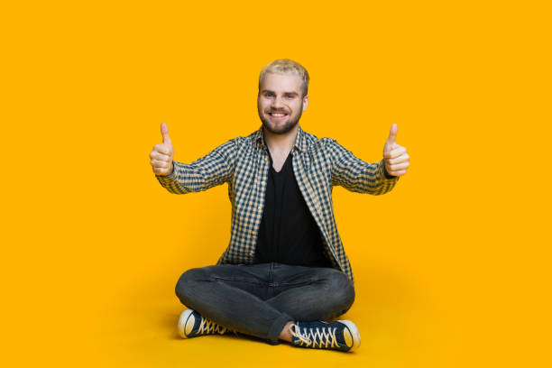 Blonde caucasian man with beard is sitting on a yellow wall and gesturing the approbation sing Blonde caucasian man with beard is sitting on a yellow wall and gesturing the approbation sing approbation stock pictures, royalty-free photos & images