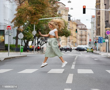 Blonde cool woman crossing street, jumping, hovering, checking phone