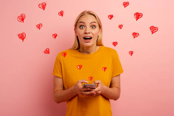 Blonde cute girl receives hearts on her smartphone. Happy and surprised expression face. Pink background - foto stock