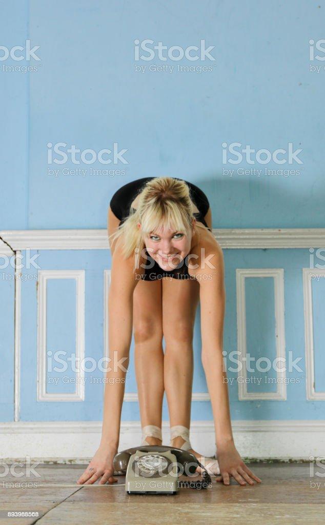 Blonde Damish ballerina bent double behind antique telephone stock photo