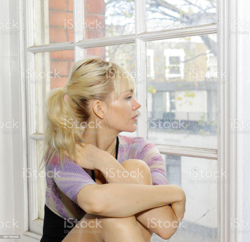 Blonde Danish ballerina arms around knees in old window London stock photo