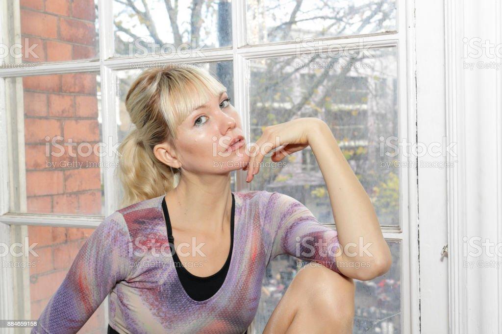 Blonde Danish ballerina chin resting on hand in old window London stock photo