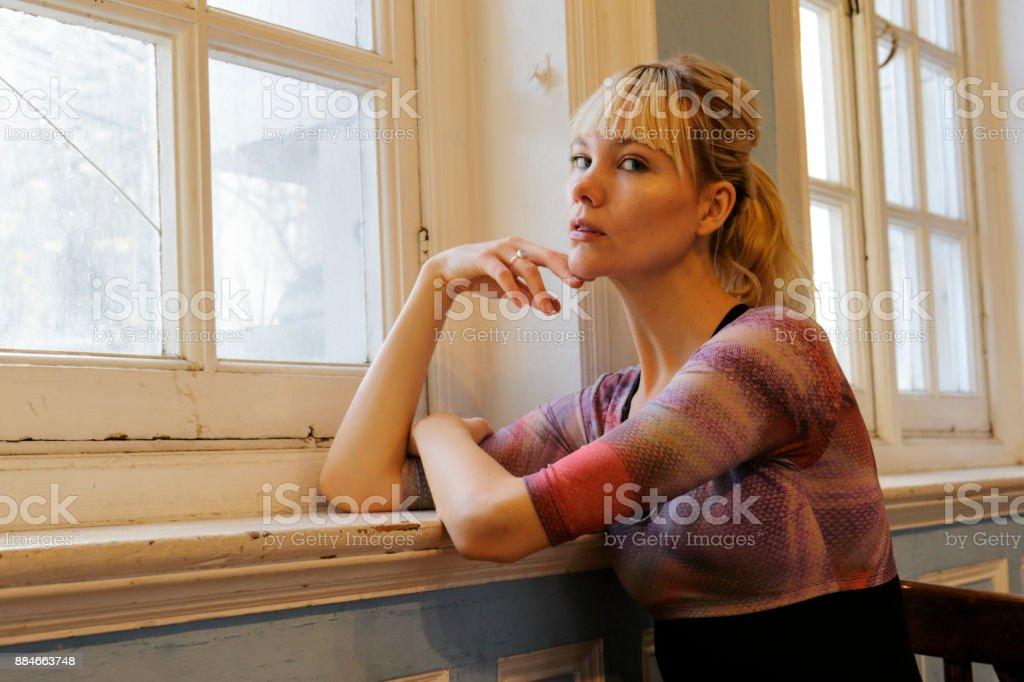 Blonde Danish ballerina chin resting on hand in soft window stock photo