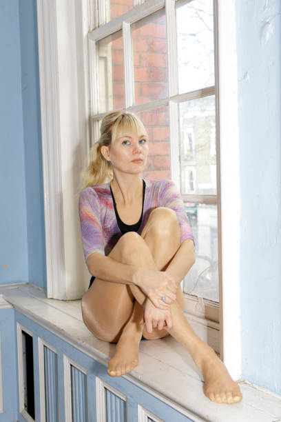 blonde danish ballerina hugging knees on window sill london - whiteway ballet stock photos and pictures