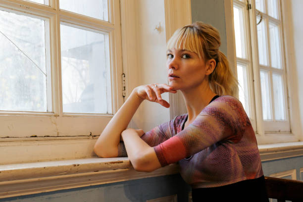 blonde danish ballerina thoughtful leaning in old window london - whiteway danish stock photos and pictures
