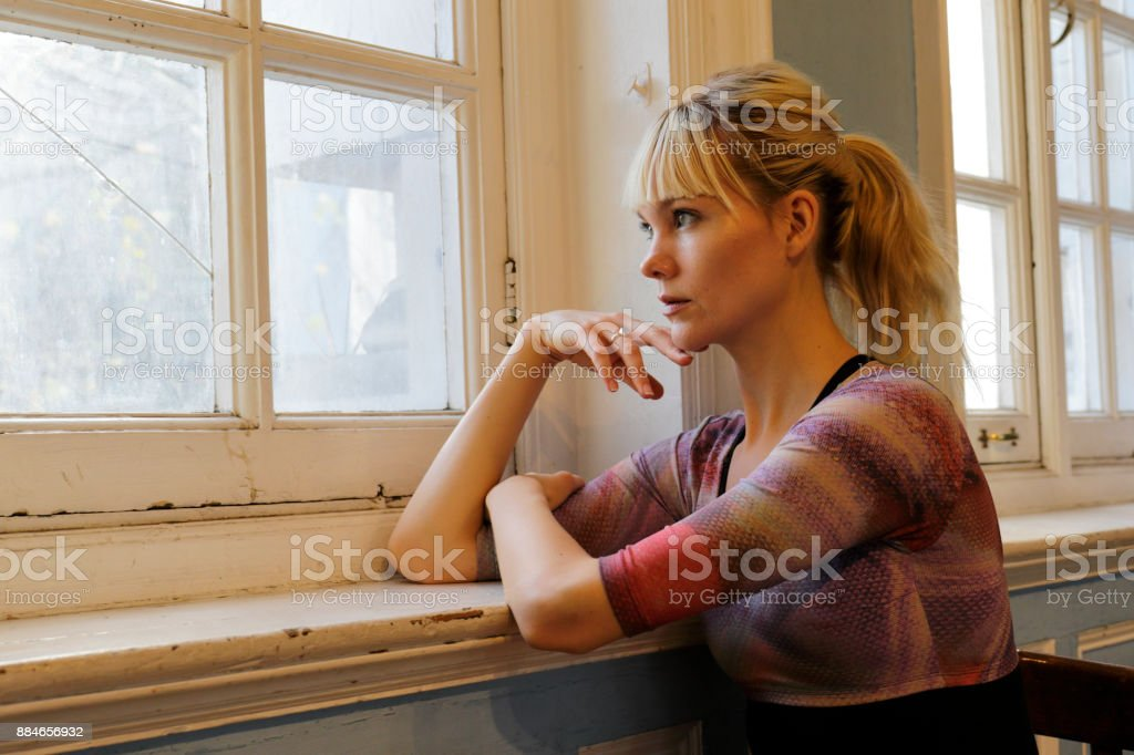 Blonde Danish ballerina thoughtful leaning in old window London stock photo