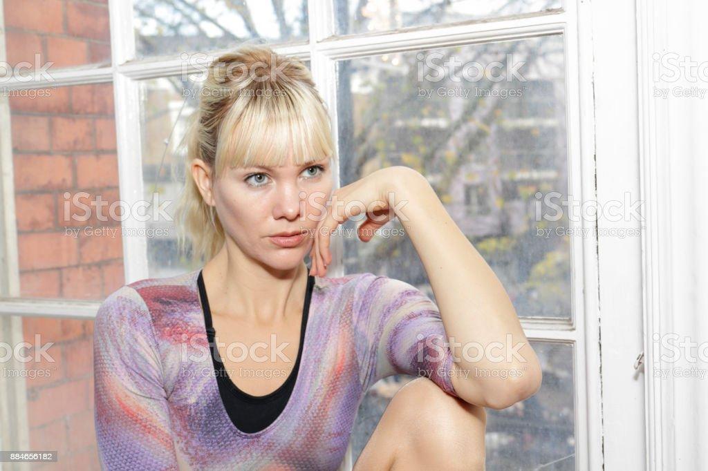 Blonde Danish ballerina thoughtful seated on old window ledge stock photo