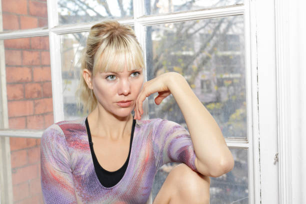 blonde danish ballerina thoughtful seated on old window ledge - whiteway danish stock photos and pictures