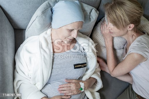 928968772 istock photo Blonde daughter and ill and sad mother laying in bed together. Home cancer treatment concept 1146761789