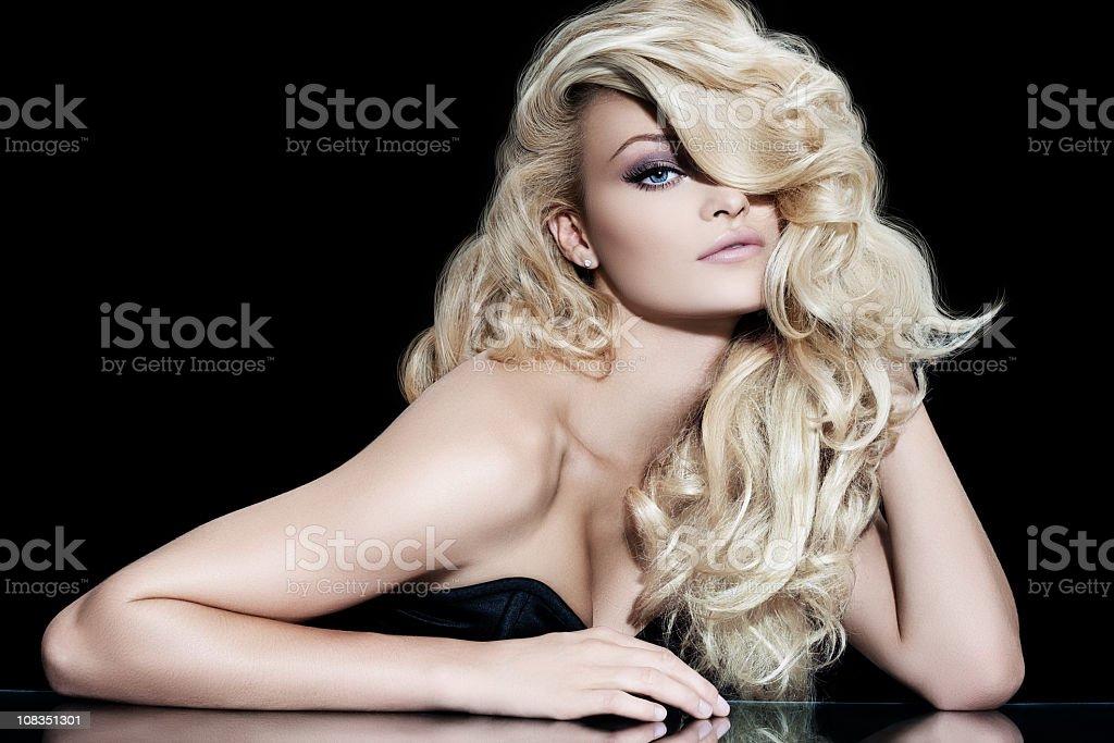 Blonde diva fashion model posing against black background royalty-free stock photo