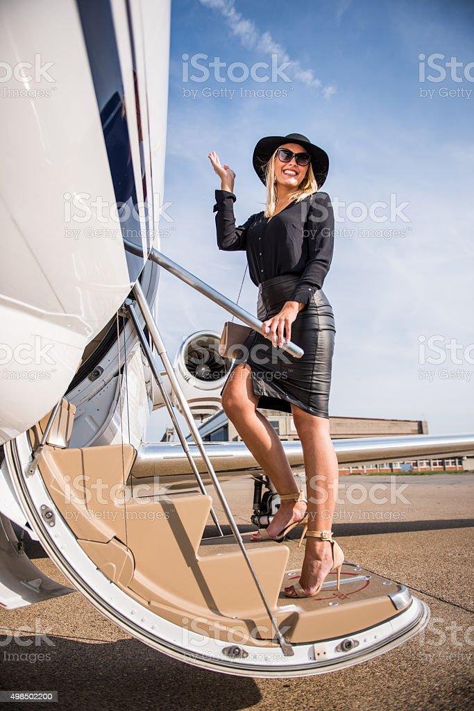Blonde elegant woman entering private jet airplane stock photo