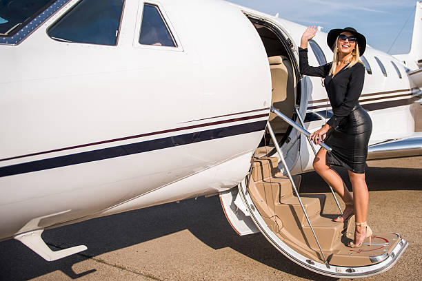 Blonde elegant woman entering the airplane stock photo