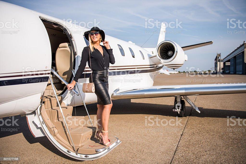 Blonde elegant woman exiting from jet aeroplane stock photo