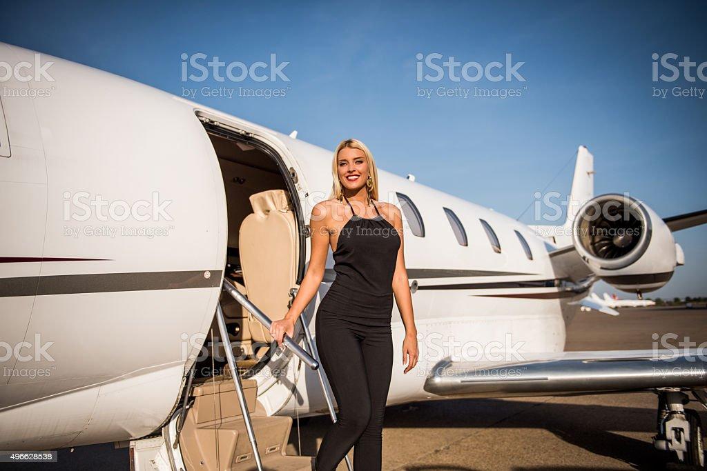 Blonde elegant woman exiting private aeroplane stock photo