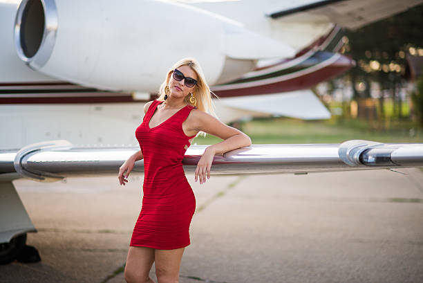 Blonde elegant woman next to wing of jet airplane stock photo