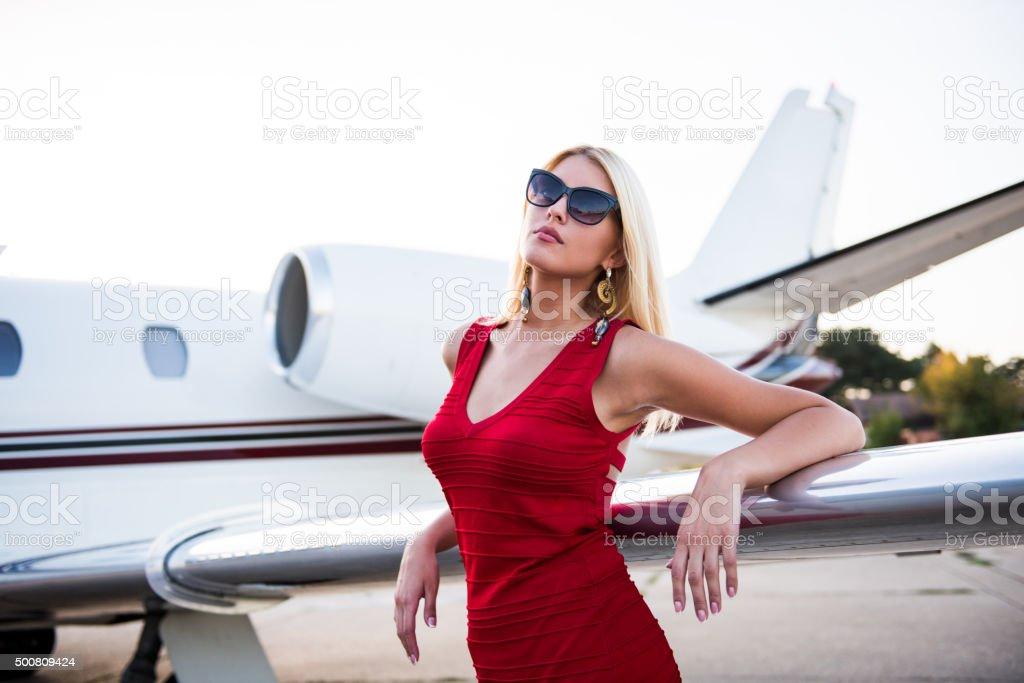 Blonde elegant woman standing next to aeroplane wing stock photo