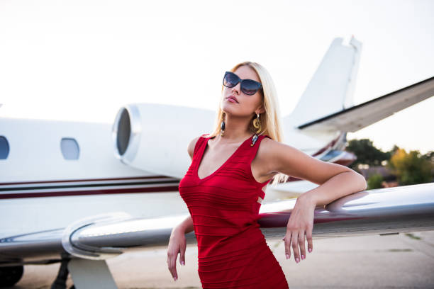 Blonde elegant woman standing next to aeroplane wing stock photo