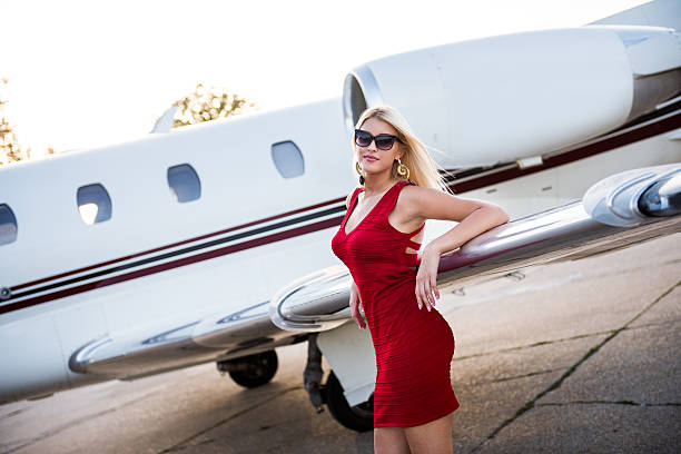 Blonde elegant woman standing next to wing of an airplane stock photo