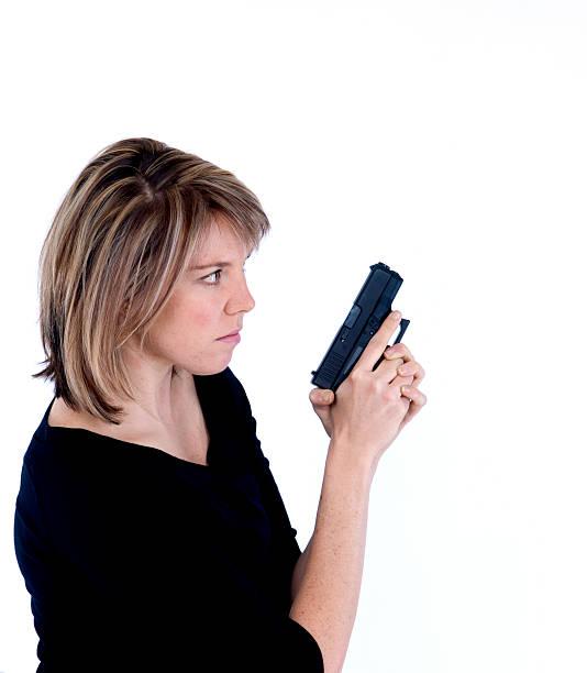 Blonde female on guard with handgun stock photo