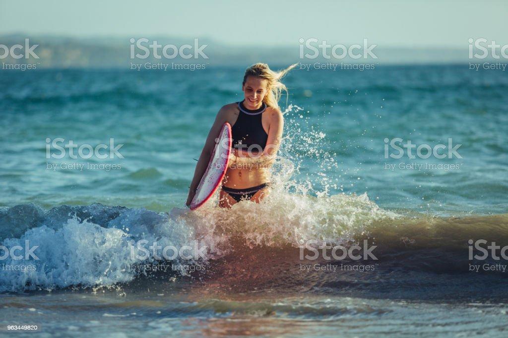 blonde femme surfer avec planche de surf dans l'eau - Photo de Activités de week-end libre de droits