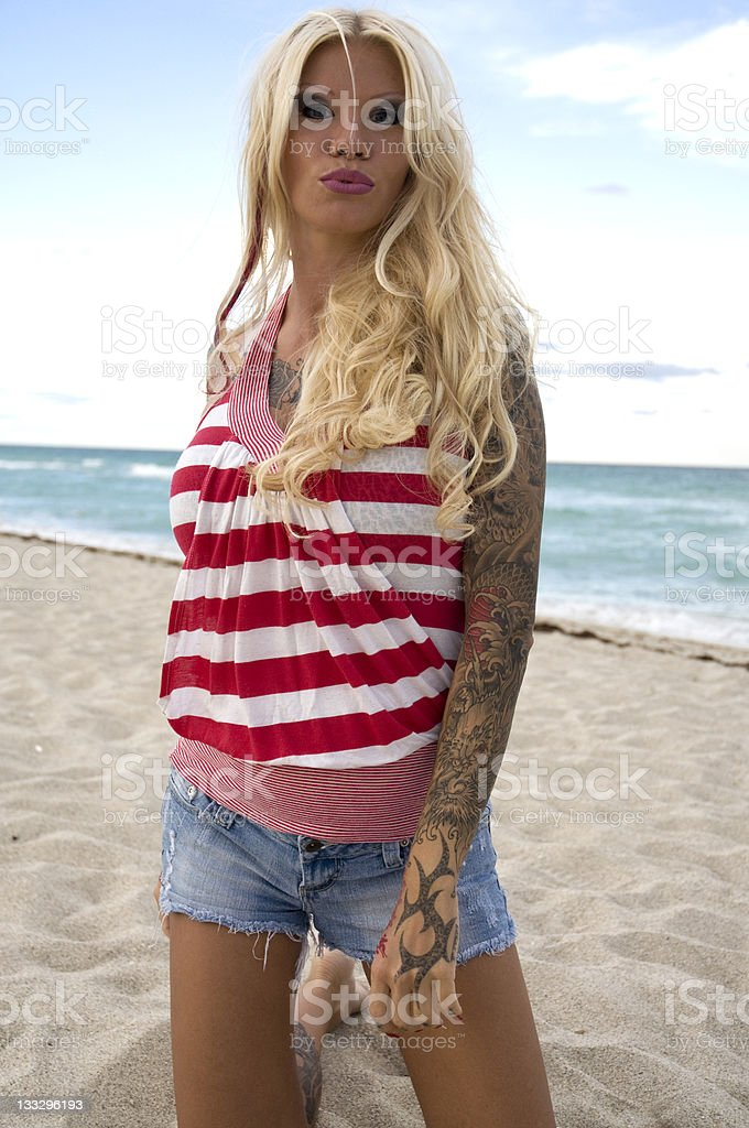 Blonde Female Tattoo Girl Pose On Beach stock photo